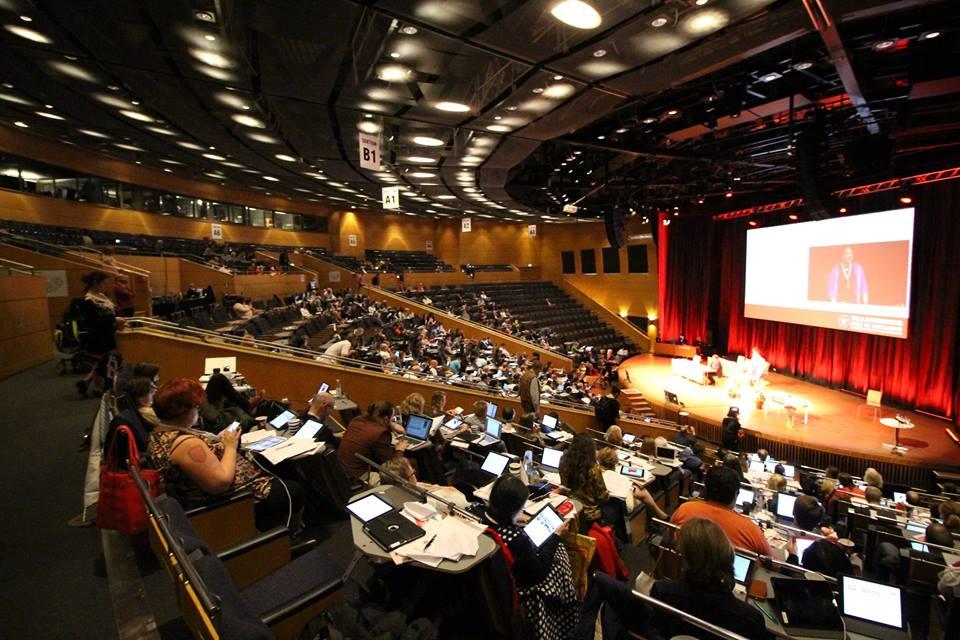 Syntolkning: Foto på ledamöterna i sina bänkar i kongresshallen och predidiet på scenen.
